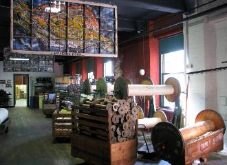 Giant spools, loaded mill carts, contemporary artwork (hanging), and textile machinery are part of the exhibits at Museum L-A inside the 1850s Bates Mill. Credit: Maine Office of Tourism